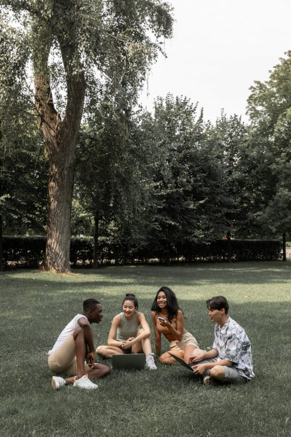 multiracial friends gathering in summer park