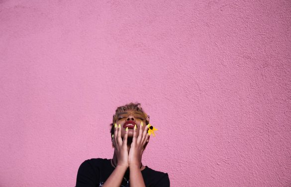 trendy young black woman touching face while throwing head back on pink background
