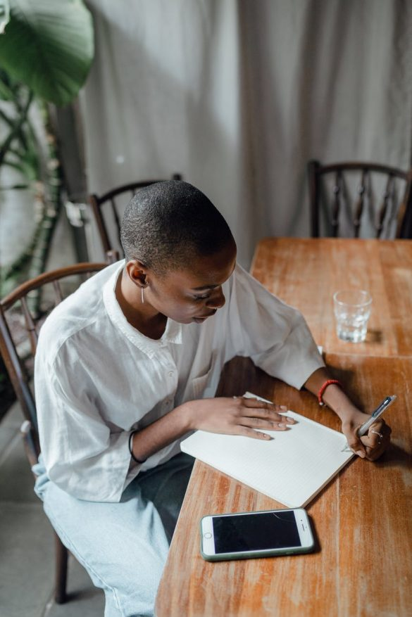 focused black left handed woman writing notes