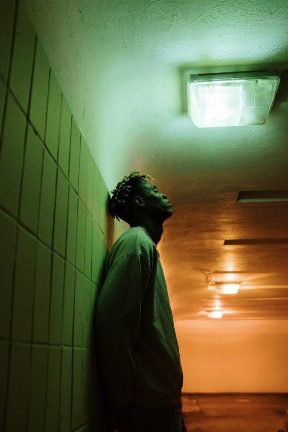 man in gray dress shirt standing beside white wall