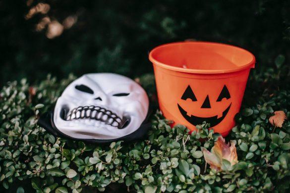 spooky skeleton mask placed near orange bucket outdoors