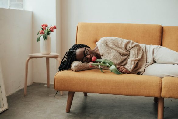 romantic woman with blooming flowers lying on sofa
